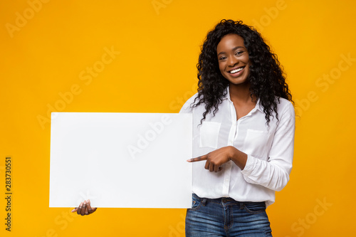 Fotobehang - Afro girl is holding yellow advertising board