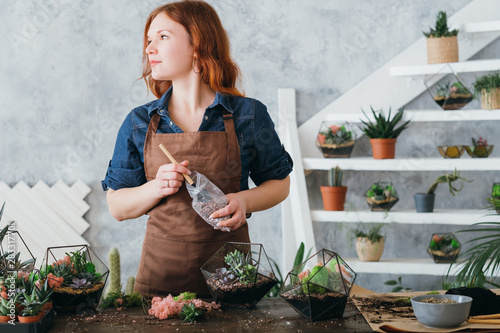 Fotobehang - DIY florarium. Plants growing hobby. Woman working on new decorative arrangement, using glass vases and gravel for succulents.