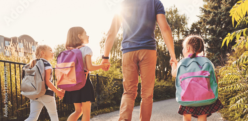 Fotobehang - Parent and pupils are going to school