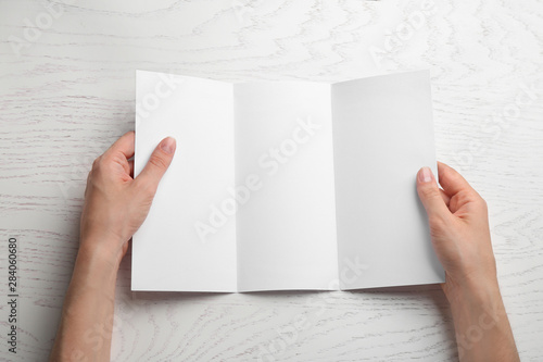Fotobehang - Young woman holding blank brochure at white wooden table, top view. Mock up for design