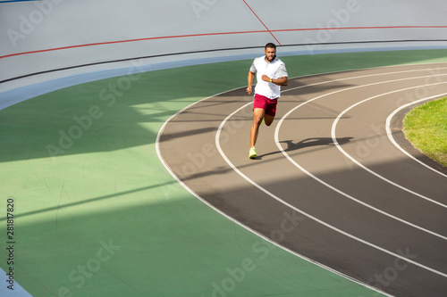 Fotobehang - African American athlete running on the running track