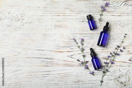 Fotobehang - Bottles of essential oil and lavender flowers on white wooden background, flat lay. Space for text