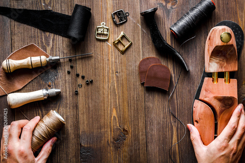 Fotobehang - cobbler tools in workshop dark background top view