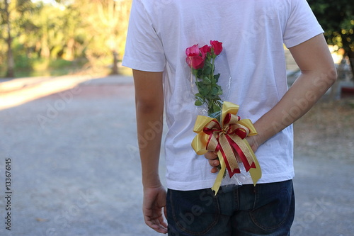 Fotobehang Young man hiding red roses behind his back for surprise his girlfriend in honor of Valentine's day
