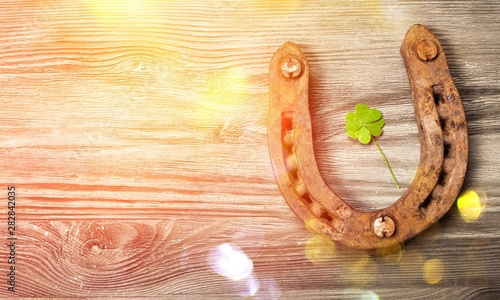 Fotobehang - Rusty metal horseshoe with a leaf of clover on a wooden table