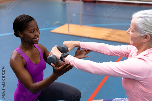 Fotobehang - Female trainer assisting disabled senior woman to exercise with dumbbell in sports center