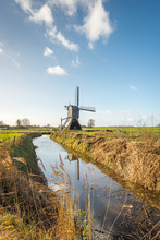 Fotobehang - Dutch polder mill at the end of a stream